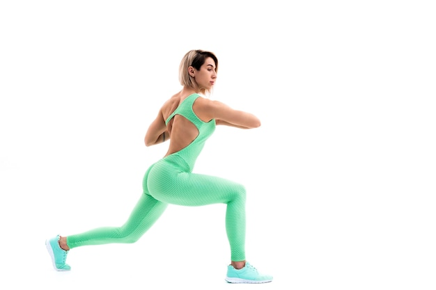 Full body portrait of young sporty woman stretching