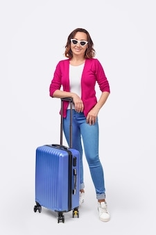 Full body positive adult woman in sunglasses smiling and standing with blue suitcase on white background