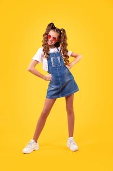 Позитивный ребенок в стильном джинсовом платье и солнцезащитных очках, держащий руки за талию и улыбающийся