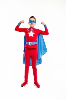 Full body powerful boy in superhero costume with cape and mask showing biceps against white