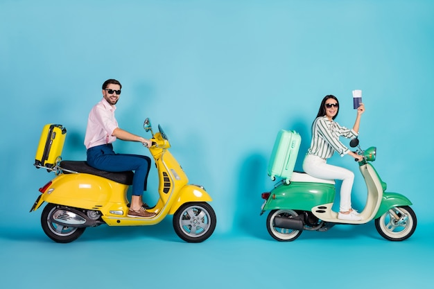 Full body profile photo of cool lady guy two retro moped suitcases fixed behind celebrity vip showing tickets not stop driving formalwear outfit isolated blue color wall