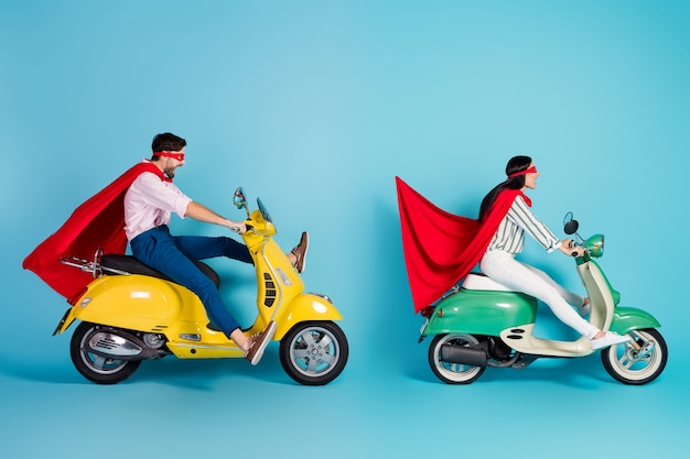 Full body profile photo of crazy lady guy drive two retro moped big speed brakes stop wear red cape mask playing party super heroes role coat fly air isolated blue color wall