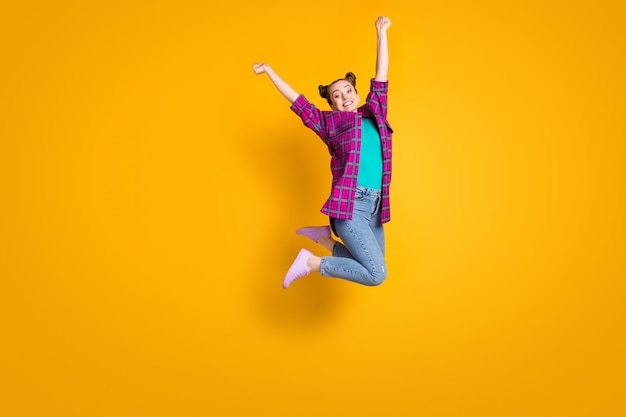 Full body profile photo of crazy teen lady jump high up air flight champion sports competition overjoyed wear casual plaid shirt shoes sneakers jeans isolated yellow color background