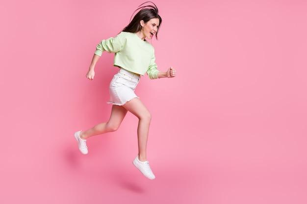 Полное фото профиля привлекательной смешной леди, прыгающей высоко в спешке покупателя в торговом центре, повседневный пуловер с обнаженным животом, юбка, туфли, изолированные на розовом фоне пастельных тонов