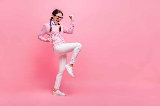 Полное фото профиля привлекательной студентки, поднимающей кулаки, празднует отличную оценку, тестовый экзамен, лучшая оценка группы, одежда, рубашка, брюки, обувь, изолированные, пастельно-розовый цвет фона