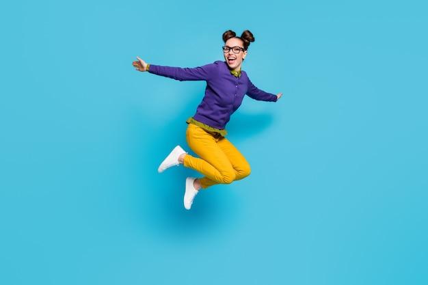 Полная фотография профиля сумасшедшей дамы две булочки прыгать высоко праздновать каникулы, выходные, ликование, размахивать руками, носить спецификации, рубашка, пуловер, штаны, изолированный синий цвет фона