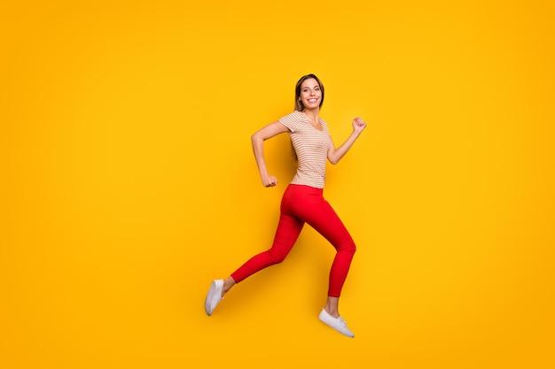 ファンキーな女性のジャンプの全身プロフィール写真急いで割引ショッピングストア中毒者はカジュアルなストライプのtシャツ赤いズボン孤立した黄色の色の壁を着用します Premium写真