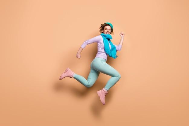 Полная фотография профиля смешной дамы прыгает высоко, спешит шоппинг распродажа скидка открытие сезона фиолетовый джемпер зеленые брюки сапоги синий берет шарф изолированный бежевый цвет фона