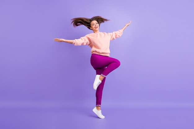 보라색 벽에 높이 점프하는 여자의 전신 프로필 사진