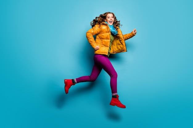 Фотография профиля в полный рост симпатичной дамы, прыгающей высоко, стремительно низкой цены, шоппинговой одежды, повседневного желтого пальто, шарфа, пурпурных штанов, красных туфель, изолированной стены синего цвета
