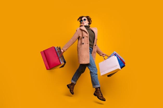 예쁜 쇼핑객 레이디 워크 쇼핑 센터의 전신 프로필 사진은 많은 팩을 착용 태양 사양 캐주얼 핑크 코트 풀오버 청바지 레오파드 프린트 신발