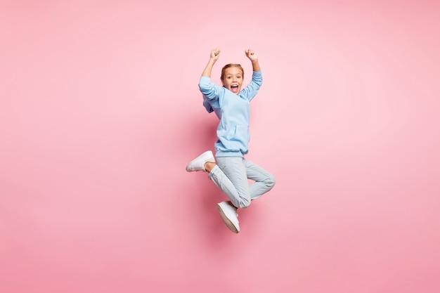 Полное фото профиля довольно маленькой леди, прыгающей высоко, празднуя победу в лучшем спортивном соревновании, носит повседневную одежду, изолированный пастельно-розовый цвет фона