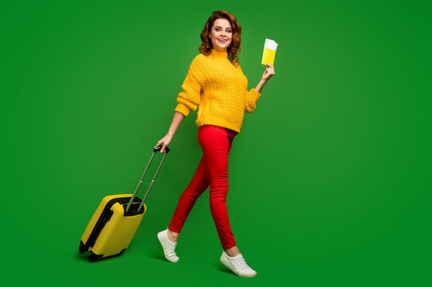 Full body profile photo of pretty lady hold tickets documents tour abroad rolling suitcase walk flight registration wear yellow sweater red pants shoes isolated green color wall