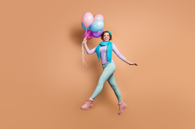 Full body profile photo of pretty lady jump high carry many air balloons walk surprise party wear violet jumper green pants boots blue beret scarf isolated beige color background