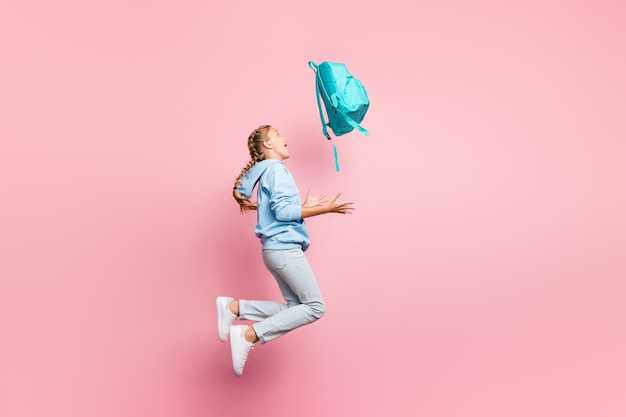 Full body profile photo of pretty little lady jumping high go home after studying week throwing pupil backpack up air wear casual sweater clothes isolated pink color background