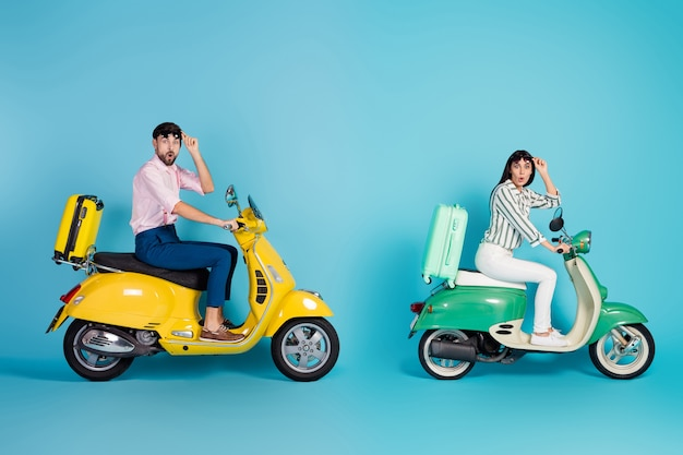 Full body profile photo of shocked lady guy drive two retro moped rush hour suitcases fixed behind travelers taking off sun glasses formalwear outfit isolated blue color wall