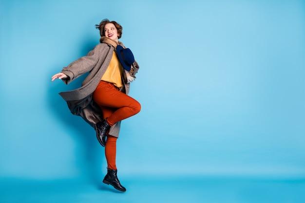 평온한 아가씨의 전신 프로필 초상화는 높은 홀드 세련된 복고풍 모자 좋은 분위기 좋은 하루 착용 캐주얼 긴 회색 코트 스카프 바지 부츠를 점프합니다.