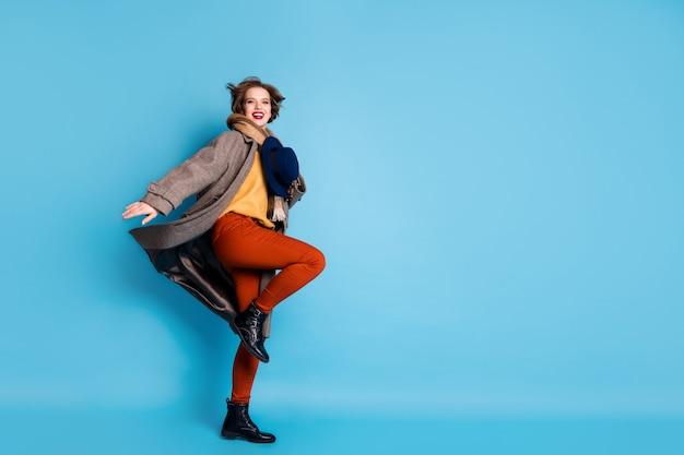 세련된 복고풍 모자 좋은 분위기 좋은 하루 착용 캐주얼 긴 회색 코트 스카프 바지 부츠를 들고 높은 점프 예쁜 아가씨의 전신 프로필 초상화.