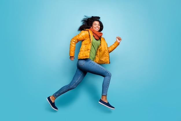 全身プロファイルきれいな女性ジャンプウェアオーバーコートジーンズ緑のセータースカーフ孤立した青い壁