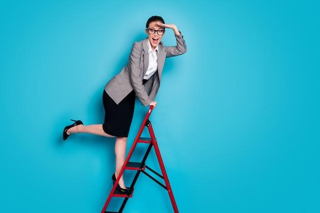 전신 프로필 측면 사진 놀란 은행가 등반 사다리 손 눈 시계 착용 재킷 스커트 격리 된 파란색 배경