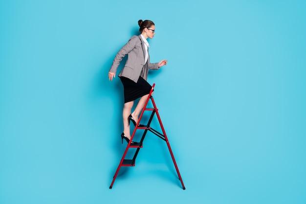 야심 찬 여성의 전신 프로필 측면 사진은 사다리 경력을 입고 블레이저 스커트 격리 된 파란색 배경을 입습니다.