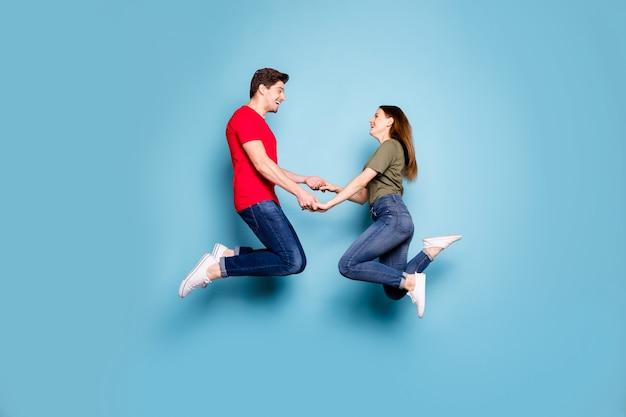 Фото сбоку в профиль в полный рост очаровательных двух супругов, расслабляющихся, отдыхающих на весенних праздниках, прыжков, держащихся за руки, чувство удовлетворения, одежда в повседневном стиле, изолированная на синем цветном фоне