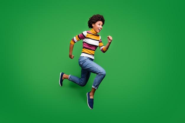 미친 쾌활한 아프리카 계 미국인 여자 점프의 전신 프로필 측면 사진 가을 할인 후 실행 기분 밝은 옷을 입고 파란색 운동화를 기뻐하십시오