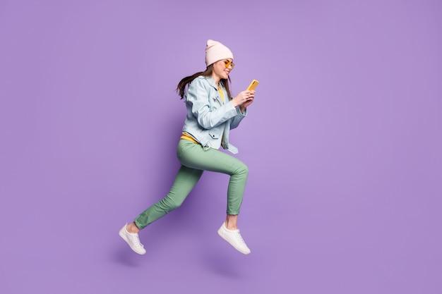 전신 프로필 측면 사진 긍정적인 소녀 점프 달리기는 스마트폰을 사용하여 소셜 미디어 재포스트 포스트 착용 가죽 재킷 녹색 바지 바지 노란색 선글라스 격리 보라색 배경