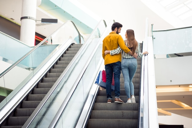 魅力的な女性のハンサムな男のカップルの後ろ姿の全身リア写真は、屋内でカジュアルなジーンズシャツの服を抱き締めてエスカレーターショッピングセンターを上に移動するバッグを運ぶ自由な時間を過ごします