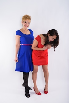 Full body shot of happy senior asian woman and young beautiful woman smiling and bending back against white background