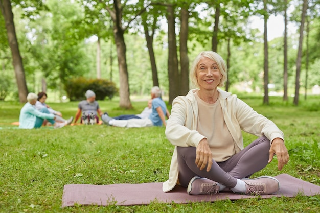 Full body shot of happy senior woman with gray hair sitting on mat in park with legs crossed smiling at camera