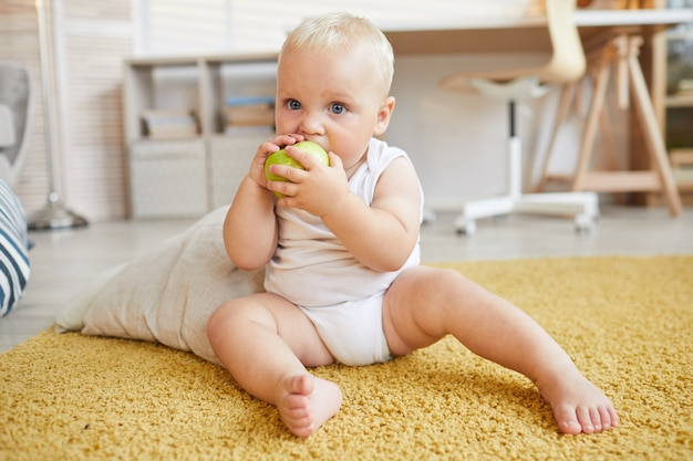 Снимок всего тела, на котором ребенок сидит на ковре, кусает и ест зеленое яблоко
