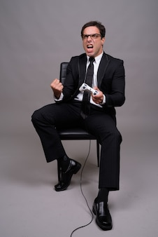 座っているとゲームをプレイするビジネスマンの全身ショット