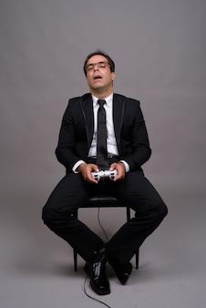 Снимок всего тела бизнесмена, сидящего и играющего в игры