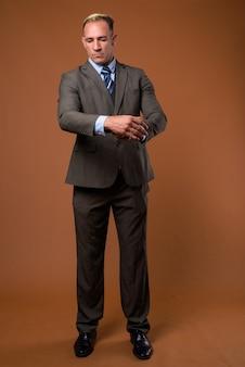 茶色の上に立っているビジネスマンの全身ショット