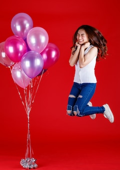 キュートで美しいアジアの女の子がジャンプして、赤い背景に面白くて幸せな笑顔でカラフルな気球で遊んでいる全身ショット、スタジオライト撮影。祭りとコンセプトを祝います。