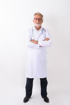Снимок всего тела счастливого старшего бородатого мужчины-врача, улыбающегося, стоя со скрещенными руками на белом