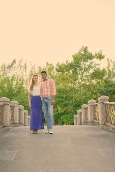 평화로운 녹색 공원의 다리에 사랑에 함께 서있는 다중 민족 부부의 전신 샷