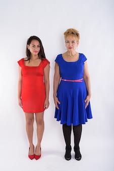 Снимок всего тела пожилой азиатской женщины и молодой красивой женщины, стоящей вместе на белом фоне