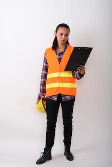 젊은 아시아 여성 건설 노동자의 전신 샷 서서 공백에 대해 하드 모자를 들고 클립 보드에 읽기