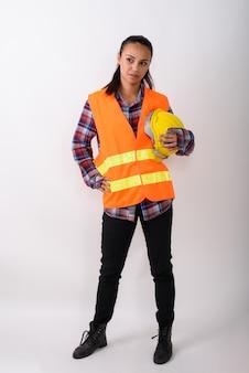젊은 아시아 여성 건설 노동자의 전신 샷 서서 공백에 대해 하드 모자를 들고 생각