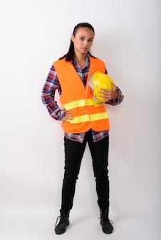 공백에 대해 하드 모자를 들고 서있는 젊은 아시아 여성 건설 노동자의 전신 샷