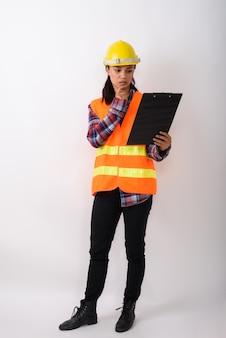 클립 보드에 읽고 공백에 대해 생각하는 동안 서 젊은 아시아 여성 건설 노동자의 전신 샷