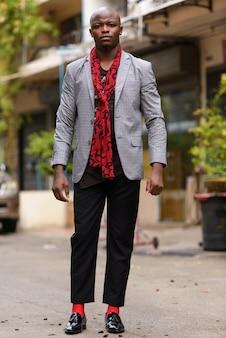 야외에서 스카프로 젊은 대머리 아프리카 사업가의 전신 샷