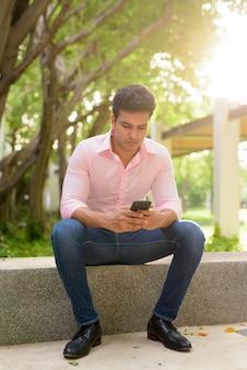 Снимок всего тела молодого красивого индийского бизнесмена, сидящего в парке по телефону