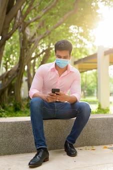 電話を使用して公園に座っているマスクを持つ若いインドのビジネスマンの全身ショット