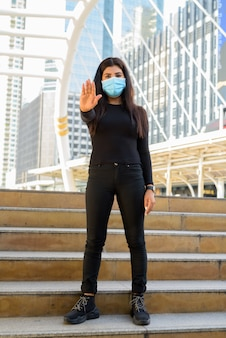 市内の階段で停止ジェスチャーを示すマスクを持つ若いインド人女性の全身ショット