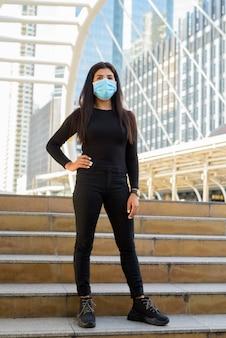 Снимок всего тела молодой индийской женщины с маской, стоящей на лестнице у моста skywalk