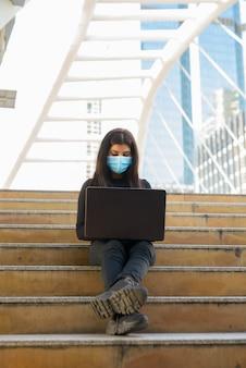 Снимок всего тела молодой индийской женщины с маской, использующей ноутбук на мосту skywalk в городе