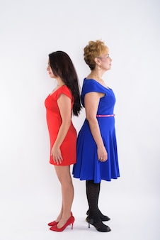 Full body shot profile view of senior asian woman and young beautiful woman standing back to back against white background